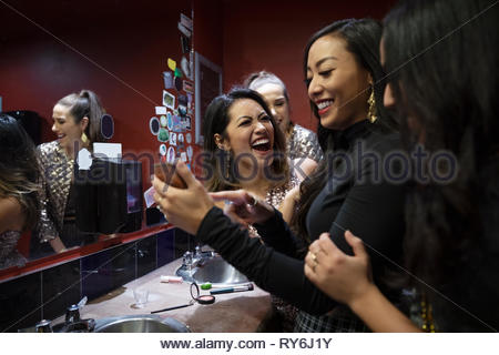 Laughing women friends using smart phone in nightclub salle de bains Banque D'Images