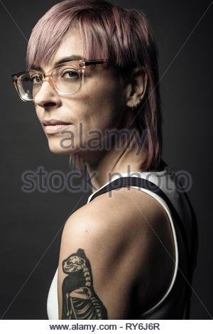 Portrait confiant belle personne de genre non-binaires aux cheveux roses, des lunettes et de tatouage Banque D'Images