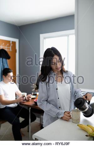 Young woman pouring coffee Latinx en cuisine le matin Banque D'Images