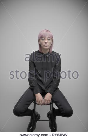 Portrait confiant belle personne de genre non-binaires aux cheveux roses Banque D'Images