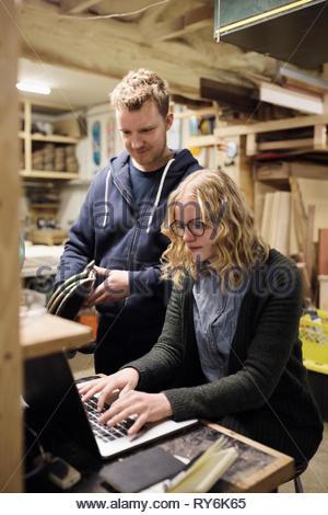 Travailleurs du bois à l'aide d'ordinateur portable en atelier Banque D'Images