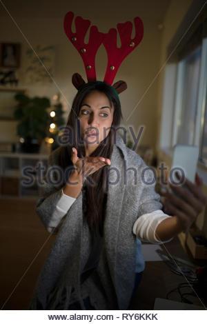 Jeune femme dans les bois de noël en tenant et en soufflant un baiser selfies Banque D'Images