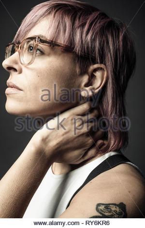 Portrait de profil non binaire réfléchi belle personne de genre aux cheveux roses et lunettes Banque D'Images