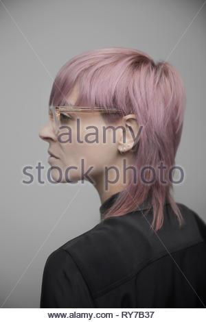 Portrait de profil confiant belle personne de genre non-binaires aux cheveux roses et lunettes Banque D'Images