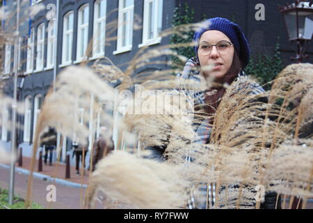 Fille cachée parmi les épis de blé ondulant dans le vent le long d'une route d'Amsterdam Banque D'Images