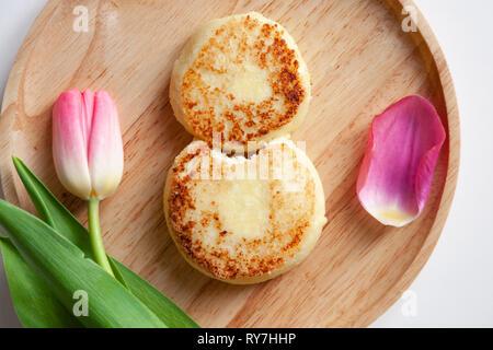 Libre de tulipe rose sur plaque ronde en bois, deux golden mordu Fried crème glacée dans la forme de la figure 8, dessert à base de fromage cottage. Con Banque D'Images