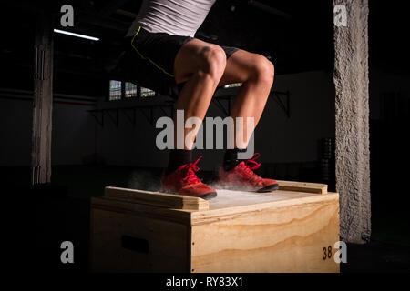 Jeune homme athlétique de récolte dans les vêtements de sport sauter sur boîte en bois entre la poussière de craie dans la salle de sport Banque D'Images