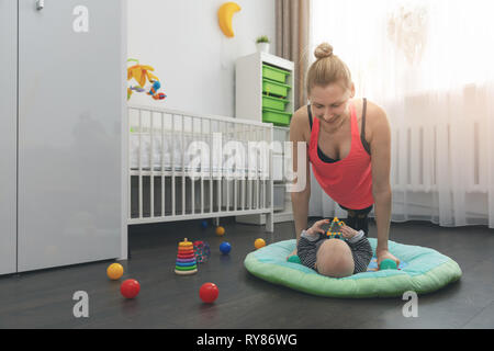 Jeune femme faisant pousser ups à la maison tout en jouant avec son petit bébé Banque D'Images