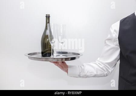 Un serveur / butler en chemise blanche et gilet costume noir portant un plateau d'argent avec une bouteille de champagne et deux verres. Arrière-plan blanc. Banque D'Images