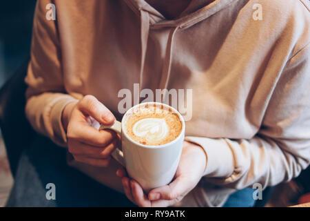 Tasse de café cappuccino avec de la mousse coeur de femmes au café, Close up