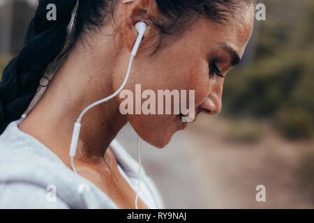 Portrait de jeune femme en bonne santé de sueur à l'extérieur permanent après son entraînement. Remise en forme avec des écouteurs femelle fatigué se reposant après l'exercice en plein air.
