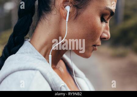 Close up de runner de sueur debout en plein air après son entraînement. Remise en forme avec des écouteurs femelle fatigué se reposant après l'exercice en plein air.