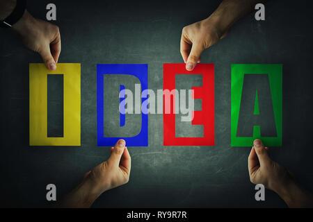 Les mains tenant un papier de couleur différente à l'idée des lettres du texte. Symbole de la collaboration, la coopération et la collaboration. Équipe d'affaires d'hiver Banque D'Images