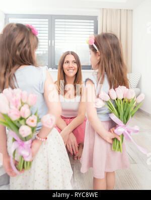 Happy mother's day concept. Jolie petite fille avec un bouquet de tulipes derrière leur dos comme un cadeau à leur mère.