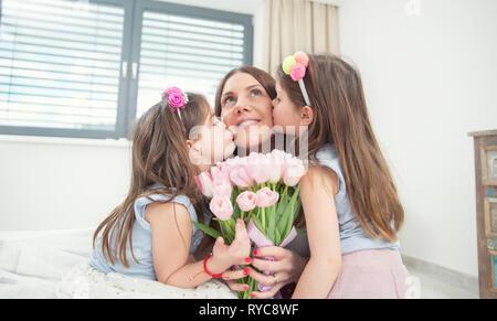 Happy mother's day concept. Peu de filles baiser leur mère des jumeaux avec un bouquet de tulipes.