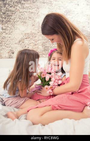 Happy mother's day concept. Maman avec twocute les jeunes filles des jumeaux sur le lit dans la chambre à coucher et un bouquet de fleurs tulipes.
