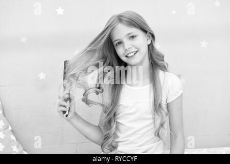 Enfant curly hairstyle tenir brosse à cheveux ou peigne. Cheveux peigne avant d'aller dormir. Habitudes de coiffure concept. Masque ou conditionneur de cheveux Peigne huile biologique. Gi Banque D'Images