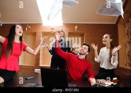 Groupe de gens d'affaires célèbre en lançant leurs documents commerciaux, dans l'air. Banque D'Images
