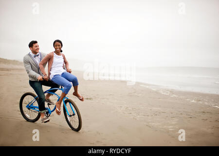Smiling young couple riding a bike le long d'une plage à marée basse. Banque D'Images