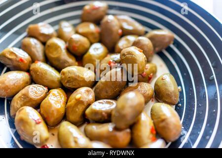 Macro closeup of green olives marinées sur la plaque en Italie ou en Grèce avec des poivrons et mélange épicé Banque D'Images