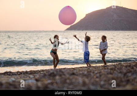 Trois jeunes enfants jouant avec un énorme ballon rose sur la plage au coucher du soleil Banque D'Images