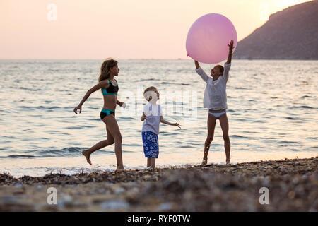 Trois enfants jouant avec un énorme ballon rose sur la plage au coucher du soleil. Frères et sœurs en vacances en mer. Banque D'Images
