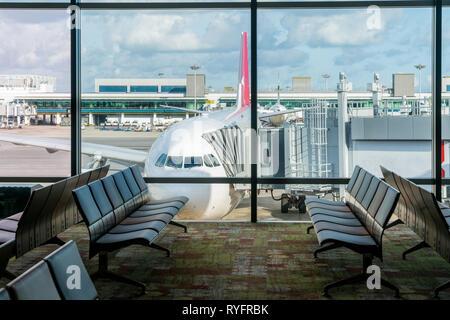 Chaises vides dans le hall des départs à l'aéroport avec parking avion. Voyage et transport à des concepts de l'aéroport. Banque D'Images
