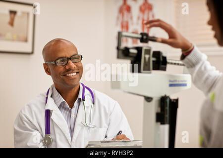 Smiling doctor en prenant des notes comme une adolescente elle-même pèse d'un poids santé à l'intérieur d'un cabinet de médecin. Banque D'Images