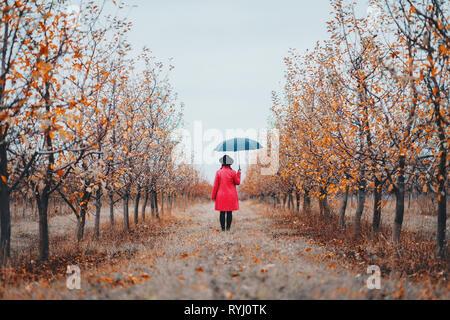 Femme en robe rouge et avec parapluie entre les arbres dans le jardin d'Apple à l'automne. Le minimalisme, voyages, nature concept.