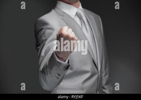 Close up.businessman clenching sa main en un poing .isolé sur fond noir Banque D'Images