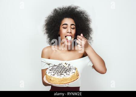 Si savoureuse! Satisfait heureux femme jeune avec les cheveux bouclés est manger son gâteau d'anniversaire blanche debout contre un arrière-plan gris. Concept d'anniversaire. Des bonbons. Concept alimentaire Banque D'Images