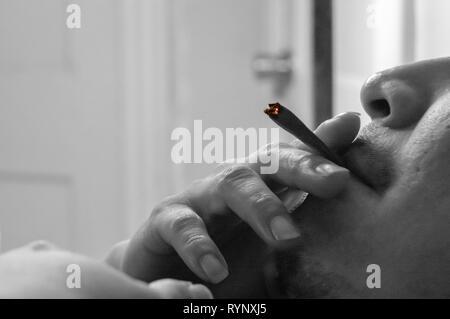 Un homme qui fume un cigare tandis que les mauvaises herbes marijuana commune fixant pour se détendre à la maison. Le noir et blanc portrait anonyme.