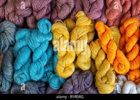 Un tas de fil à tricoter de jaune, orange, bleu et marron est prêt pour le travail. Rouge, bleu et marron Banque D'Images