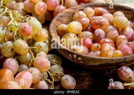 Les raisins dans un bol rose . Sur un fond de bois.