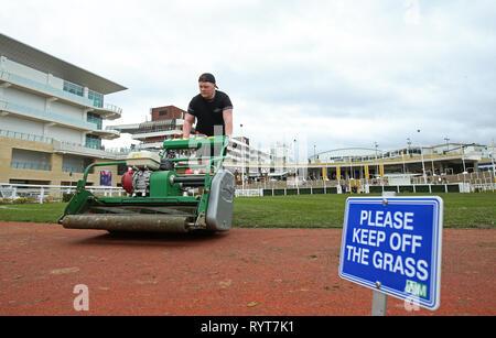 Un groundsman coupe de l'herbe avant le jour de la Gold Cup 2019 Cheltenham Festival à l'Hippodrome de Cheltenham. Banque D'Images