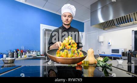 Jeune chef en remuant les légumes dans une casserole Banque D'Images