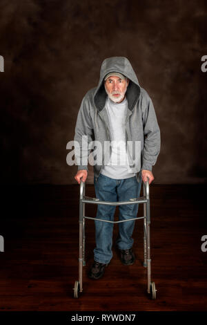 Shot vertical d'un homme âgé se reposer pendant une minute tout en marchant à l'aide d'une marchette à travers un plancher en bois. Fond brun. Capot, sur sa veste Banque D'Images