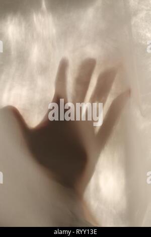 Silhouette d'une main derrière un rideau Banque D'Images