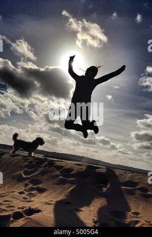 Une femme saute de joie sur une journée ensoleillée à la plage, dans le Devon, Royaume-Uni. Beau ciel bleu et nuages Banque D'Images