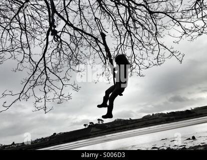 Filles balançoires sur la corde d'un arbre. Aventures sur la rivière. Banque D'Images