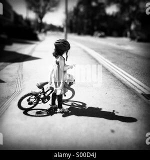 Jeune fille avec son vélo et un panier de fleurs. Ombre et soleil fort Banque D'Images