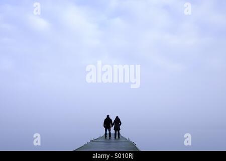 L'homme et la femme debout à la fin d'un quai brumeux holding hands Banque D'Images