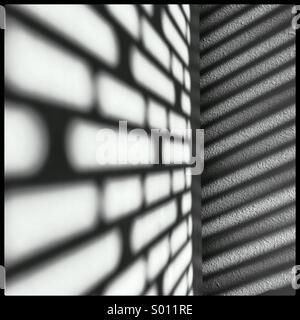 Le soleil casting cool ombres sur mon mur et l'étagère à travers les stores dans mon bureau. Banque D'Images