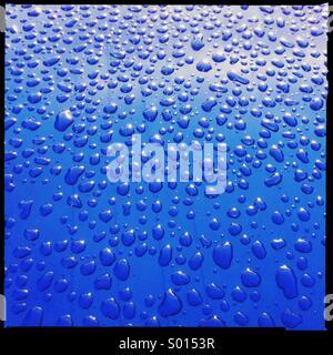 Gouttes d'eau sur une voiture bleue Banque D'Images
