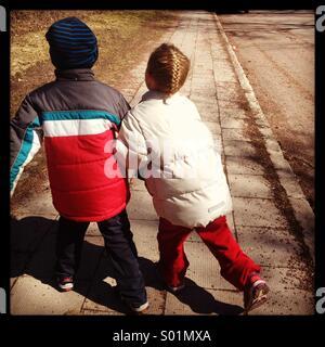 Frère sœur enfants frères et sœurs marcher bras dessus, bras dessous dans la rue se bousculer les uns les autres Banque D'Images