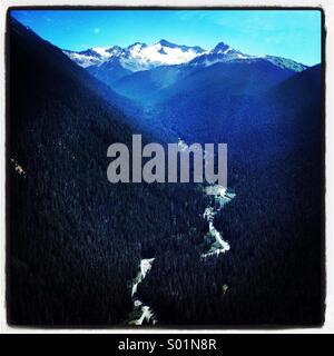 Rivière qui traverse la forêt et les montagnes, Whistler Mountain blue light Banque D'Images