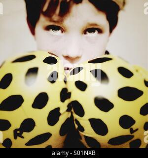 Jeune garçon portant des gants de boxe a l'air de grands yeux sur une posture défensive Banque D'Images