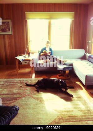 Jeune femme lisant dans la salle de séjour avec chien noir sur un tapis Banque D'Images