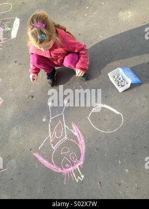 Petite fille dessin à la craie sur l'asphalte Banque D'Images