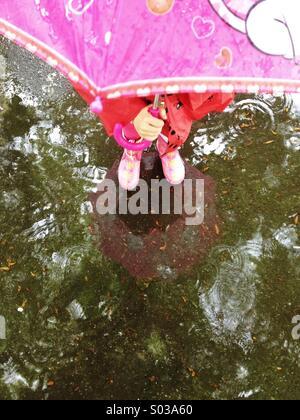 Avec parapluie enfant debout dans la flaque Banque D'Images